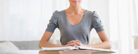 Une femme assise à un bureau, les mais entrelacées