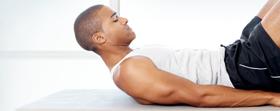 Un homme faisant des exercices abdominaux sur un tapis de yoga